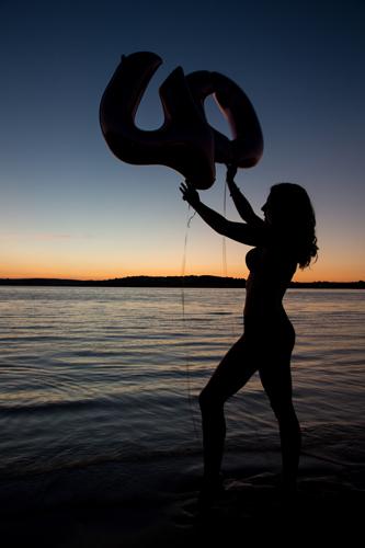 Birthday photoshoot - girl holding 40 balloons on the beach