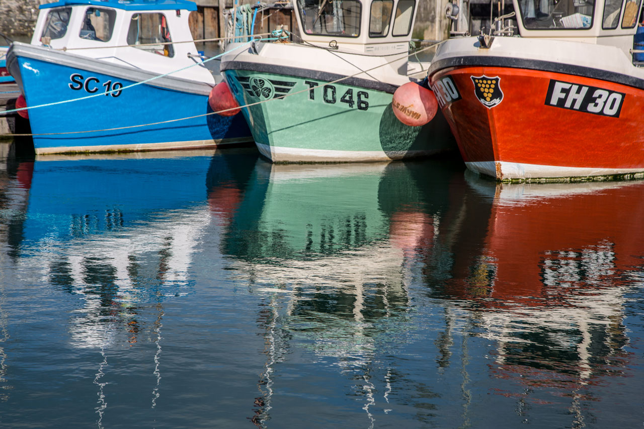 three bright fishing boats up close in Padstow Harbour.