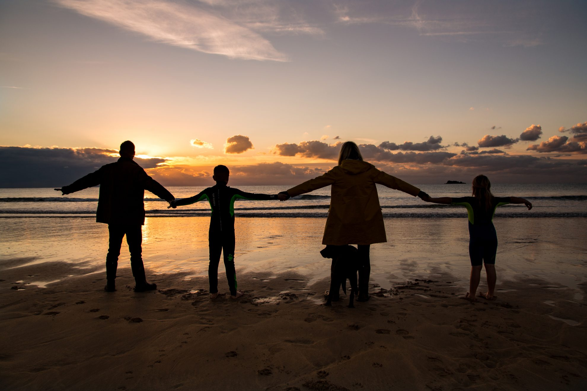 Family holding hands on the beach at Booby's Bay, near Padstow for a family photoshoot at sunset