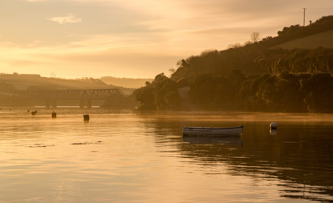 Sunrise on the Camel estuary with a lone boat and the Iron Bridge, Padstow, Cornwall